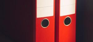 Arxivadors de color vermell que contenen les memòries anuals d'Iniciatives Solidàries.