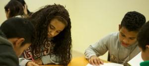 Grup de nens i nenes estudiant i fent deures al Centre Obert Gingko.