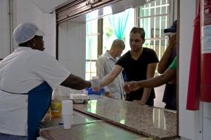 Cuinera servint menjar a un grup d'usuaris al centre d'acollida de Santa Perpètua de Mogoda.